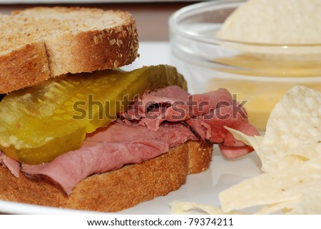 Roast beef with bread and butter pickle on whole grain toast with chips and cheese dip.