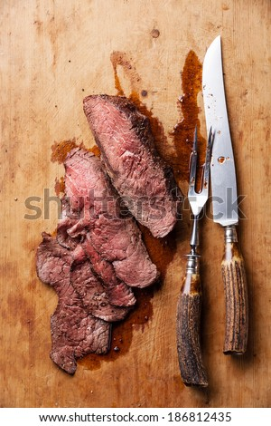 Roast beef with knife and fork for meat on wooden background