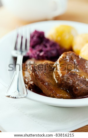Roast beef with potato dumpling and red cabbage. German cuisine