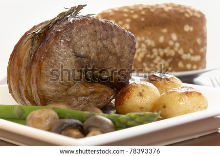 roast beef with potatoes, mushroom and asparagus.Bread in background . Shallow dof