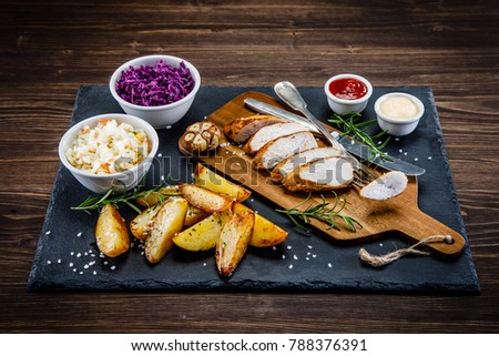 Roast chicken breast and baked potatoes on cutting board #788376391
