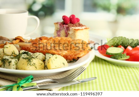 Roast chicken cutlet with boiled potatoes and cucumbers, cup of tea and dessert on green table cloth in cafe interior #119496397