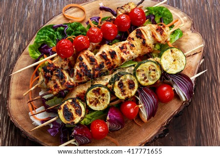 Roast Chicken filet kebab with cherry grilled on BBQ. tomatoes, zucchini and red onions on bamboo sticks.