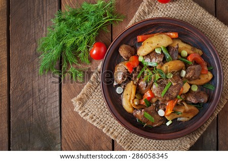 Roast chicken liver with vegetables on wooden background. Top view