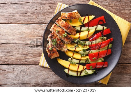 roast chicken with fresh mango, avocado and peppers with balsamic sauce close-up on a plate. Horizontal view from above