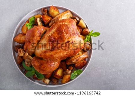 Roast chicken with roast potatoes and mushrooms on plate