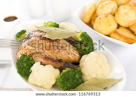 Roast Dinner - Roast partridge served with cauliflower, broccoli, roast potatoes and a jug of gravy. Traditional British Sunday and Christmas meal.