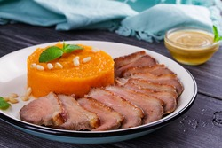 Roast duck breast and pumpkin mash, served with mint and pine nuts. Slices of duck with sweet butter squash, mustard and honey sauce. View From Above, Top Studio Shot