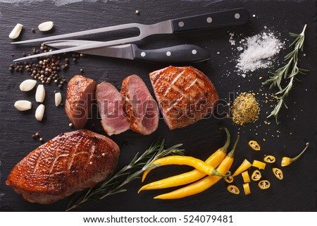 Roast duck fillet with herbs and spices closeup on a slate board. Horizontal view from above