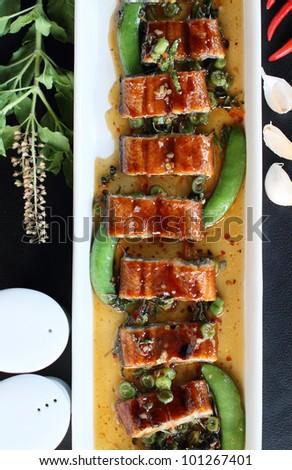 roast eel (unagi) with basil, Thai style fusion food - stock photo