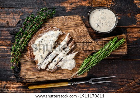 Roast fillet beef meat steak with peppercorn sauce on wooden board. Dark wooden background. Top view Stock photo ©