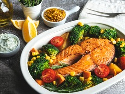 roast, fried baked fish steak salmon, trout with broccoli and carrots, corn in pot, top view