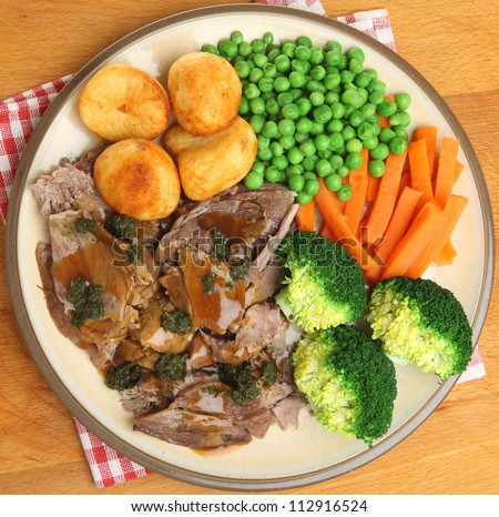 Roast lamb dinner with vefetables gravy and mint sauce.