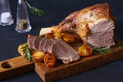 Roast leg of lamb with potatoes and rosemary on serving wooden board