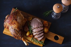 Roast leg of lamb with potatoes and rosemary on serving wooden board. View from above, top view
