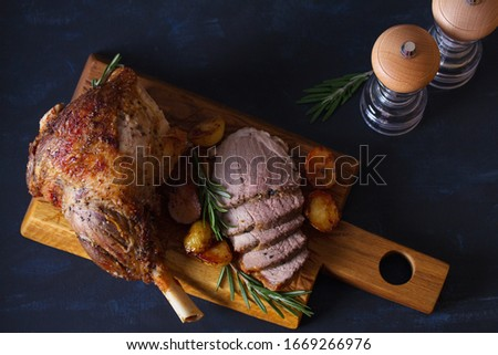 Roast leg of lamb with potatoes and rosemary on serving wooden board. View from above, top view Stockfoto ©