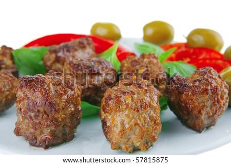 roast meat balls on basil over blue dish