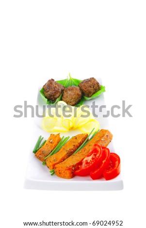 roast meatballs on basil over white plate