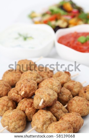 Roast meatballs on skewers with tzatziki and tomato dip and salad. Shallow DOF