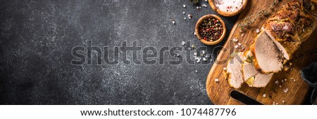 Roast pork meat with herbs and spices on black stone table. Long banner format