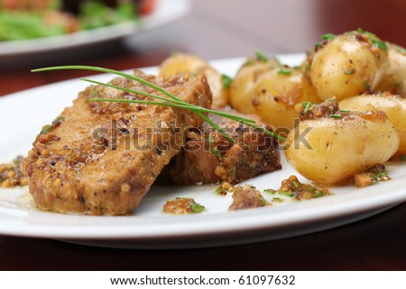 Roast pork on onion and mustard with baby potatoes