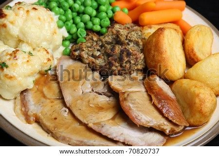 Roast pork with stuffing, roast potatoes, cauliflower cheese, peas, carrots and gravy.