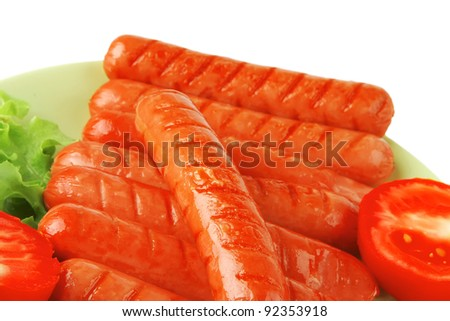 roast sausages on green dish over white