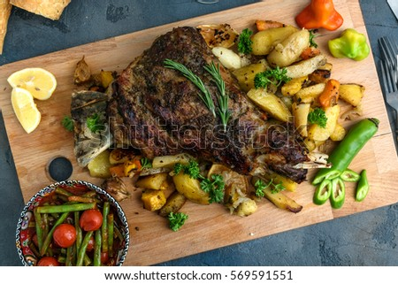 Roast shoulder of lamb on baked potato and carrots, wooden board, top view. #569591551