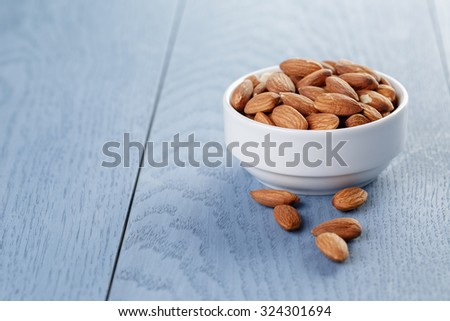 roasted almonds in white bowl on blue wooden table