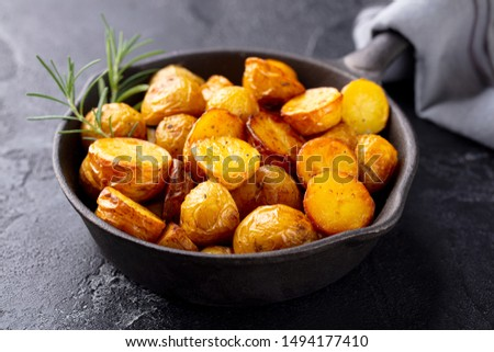 Roasted baby potatoes in iron skillet. Dark grey background. Close up.