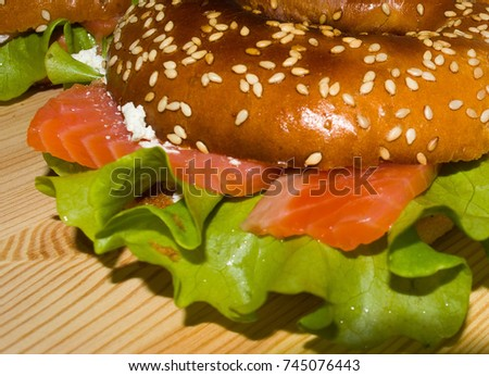 Roasted bagle with red fish , salmon and white cream cheese on wooden plate