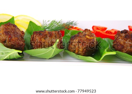 roasted beef cutlets on white with tomatoes and lemon