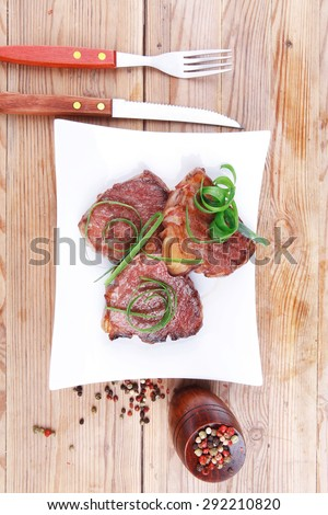 roasted beef meat strips steak on white ceramic plate with hot dry pepper on wood table