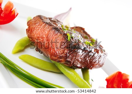 roasted beef served with tomato on white dish - stock photo