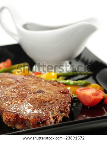 Roasted Beef with Braised Cherry Tomato and Green Asparagus on Black Dish with White Sauceboat. Isolated on White Background