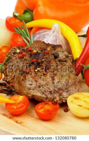 Roasted Beef with Grilled Vegetables, Spices, Peppercorns, Onion, Garlic and Herbs closeup on Wooden Board