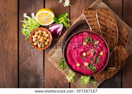 Roasted Beet Hummus with toast in a ceramic bowl on a wooden background. Top view