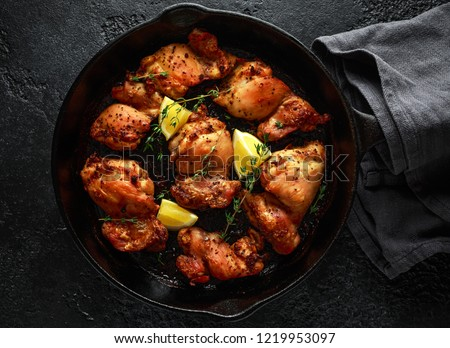 Roasted boneless skinless chicken thighs in lemon and thyme dressing served in vintage cast iron skillet, frying pan ストックフォト ©