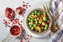 Roasted brussels sprouts, healthy vegetarian meal served on a white plate with golden cutlery on a white marble stone background with pomegranate seeds, close-up, top view