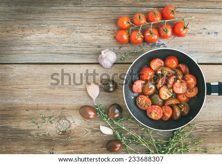 Roasted cherry-tomatoes with garlic and thyme in a cooking pan on a rustic wood background with a copy space. Top view #233688307