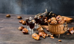 Roasted chestnuts in a copper plate with amaretto liquor, a special autumn aperitif, fresh chestnuts in a mesh bag  on a wooden table. selective focus and copy space