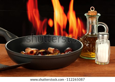 roasted chestnuts in the pan and decanter with oil, salt and pepper on wooden table close-up