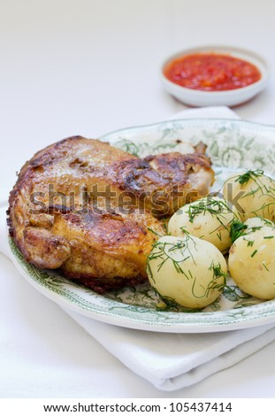roasted chicken and potato with vegetables on a white plate