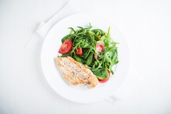 Roasted chicken breast and fresh healthy salad with tomato and greens (spinach, arugula) top view on white wooden background. Food and health. Clean eating. Healthy lifestyle