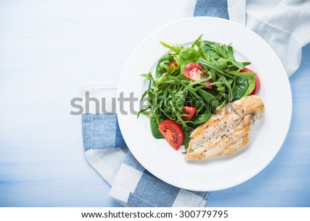 Roasted chicken breast and fresh salad with tomato and greens (spinach, arugula) top view on blue wooden background. Healthy food.