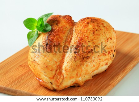 Roasted chicken breasts on cutting board