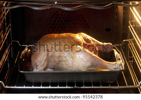 Roasted chicken cooking in black oven