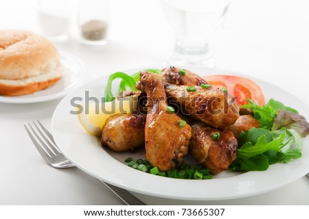 Roasted chicken drumsticks and salad on white plate