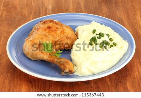 roasted chicken leg with mashed potato in the plate on wooden table close-up