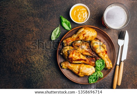 Roasted chicken legs on the dark background. Cooked with sauce from mustard and olive oil. Top view. Foto stock ©